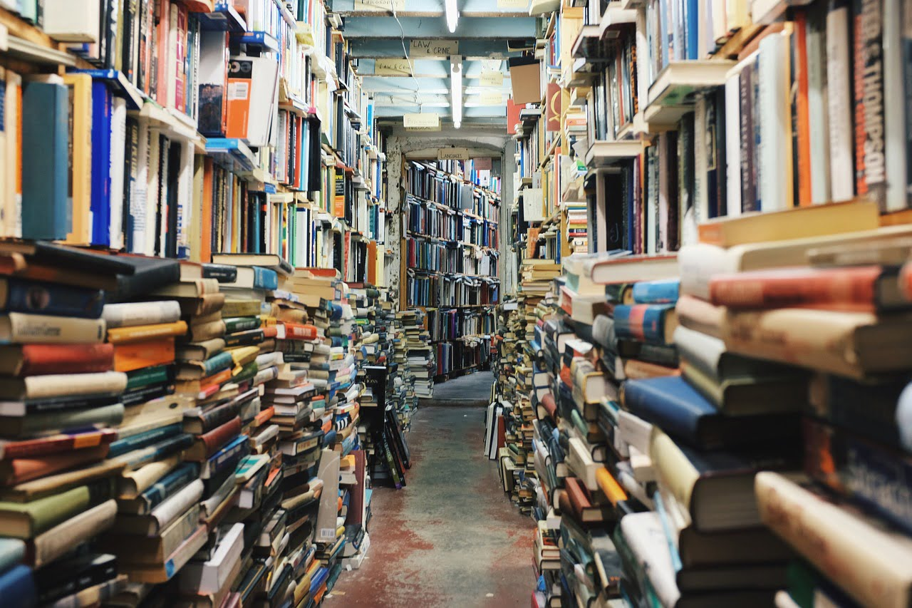 Books stacked on the floor and on shelves.