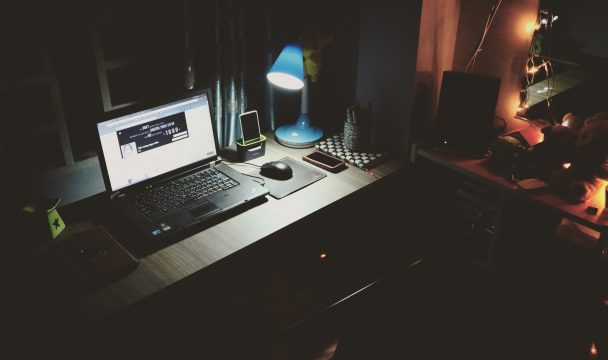 Illuminated laptop at a desk in a dark room: always on culture; you can't work 24/7