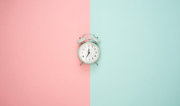 Alarm clock on a pink and blue background.