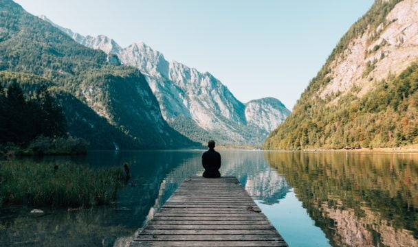 A man practices mindfulness on a pier in the mountains